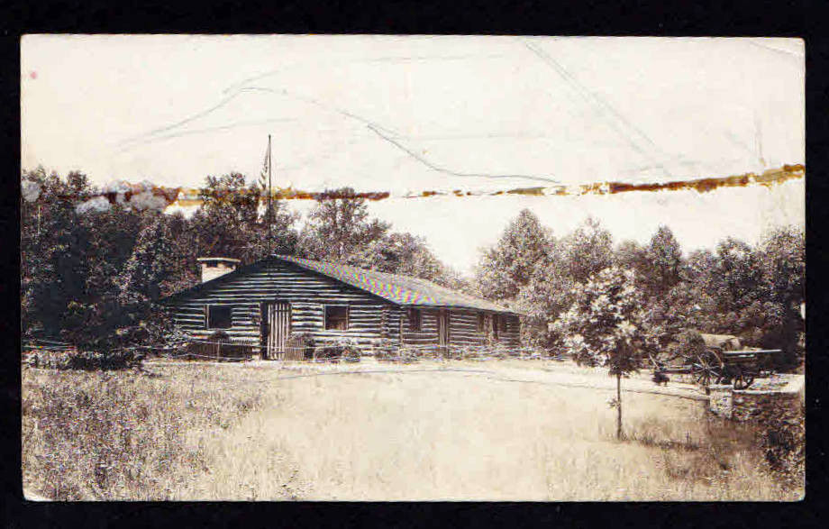 early 314th memorial log cabin photo with big guns no shells on walkway